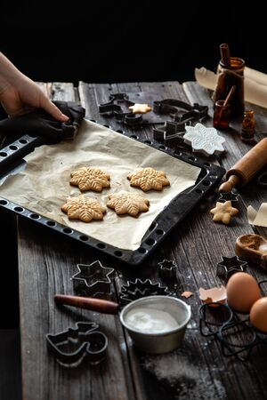 baked christmas gingerbread cookies on baking tray with parchment on rustic wooden table with rolling pin, flour and cookie cutters