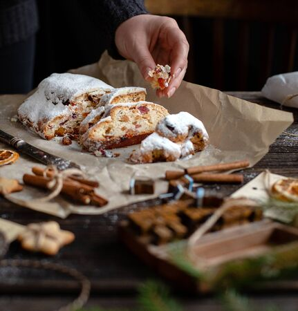sliced homemade Christmas dessert stollen with dried berries and nuts on parchment in woman hand on wooden rustic table with cinnamon, orange slices, Christmas tree branches, selective focus