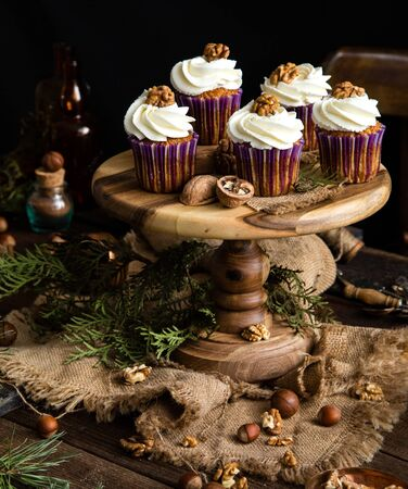 homemade carrot or pumpkin cupcakes with white cream and walnut on top in purple cupcake holders on wooden cake stand on rustic table with juniper branches, nuts, old bottles, spoons Foto de archivo - 132564118