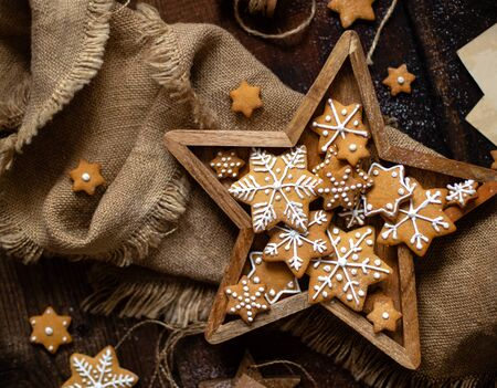 overhead shot of christmas snowflakes shaped orange cookies with beautiful icing decoration in wooden star shaped box stands on rustic brown table with sackcloth