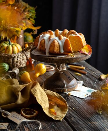 homemade tasty baked bundt pumpkin cake on wooden cake stand on rustic table with assorted small pumpkins, bouquet of autumn colorful leaves, orange napkin Foto de archivo - 132518653