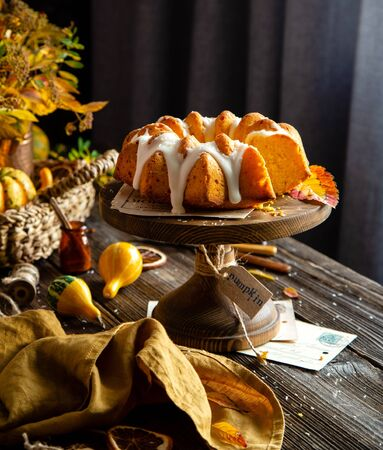 homemade tasty baked bundt pumpkin cake on wooden cake stand on rustic table with assorted small pumpkins, bouquet of autumn colorful leaves, orange napkin Foto de archivo - 132573844