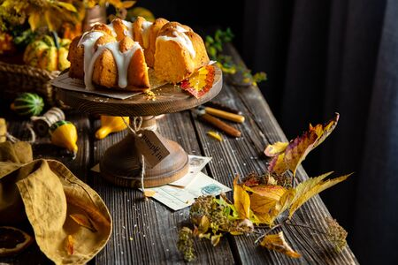 homemade tasty baked bundt pumpkin cake on wooden cake stand on rustic table with assorted small pumpkins, bouquet of autumn colorful leaves, orange napkin