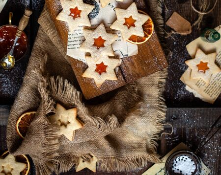 overhead shot of homemade baked star shaped christmas cookies with orange jam on wooden board on rustic table