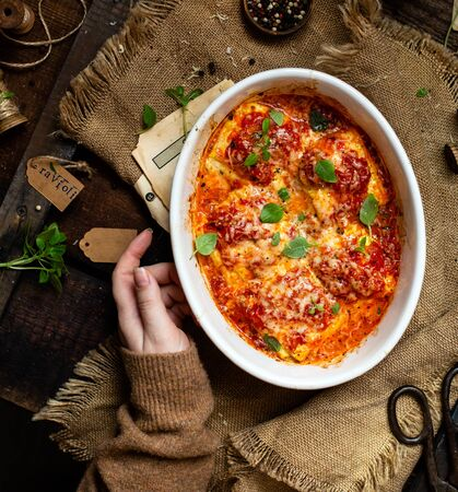 overhead shot of homemade zucchini ravioli or lasagna in tomato sauce with melted cheese, fresh basil in oval white ceramic baking pan on rustic wooden table