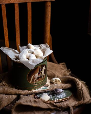 Homemade vanilla crescent cookies with powdered sugar on top in vintage christmas decorated metal box on wooden chair.