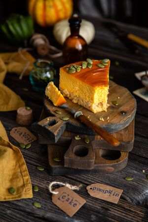 homemade slice of pumpkin cheesecake with caramel sauce and seeds on top on wooden boards on rustic wooden table with assorted small pumpkins