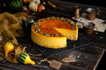 homemade pumpkin cheesecake with caramel sauce and seeds on top on metal wicker stand on rustic wooden table with assorted small pumpkins Foto de archivo - 133138139