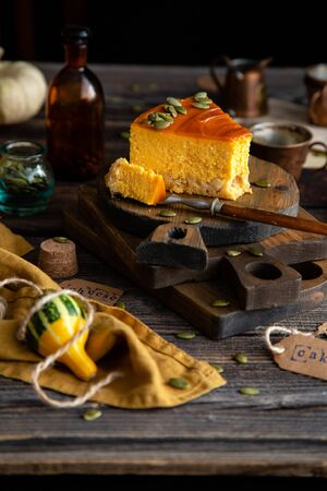homemade slice of pumpkin cheesecake with caramel sauce and seeds on top on wooden boards on rustic wooden table with assorted small pumpkins Foto de archivo - 133135633