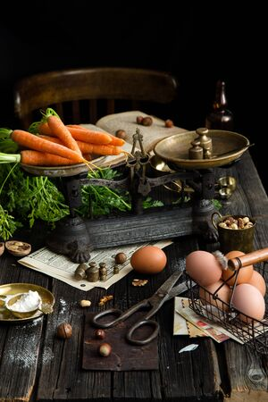 ripe tasty carrots with leaves on vintage scales stands on rustic wooden table with flour, eggs, nuts, spices. process of cooking