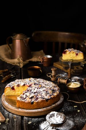 homemade tasty biscuit round cake with cherries, almond flakes, powdered sugar on top on wooden stand on rustic table with sackcloth, copper cups and teapot, forks 写真素材