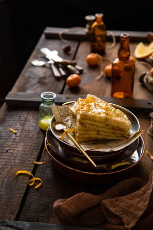 homemade stack of traditional french thin crepes suzette with orange sauce in copper plates on rustic wooden table with old bottles, tangerines, brown napkin