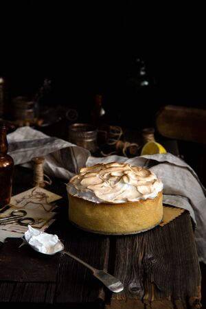 Homemade tasty baked lemon tart with shortbread crust and whipped meringue on top stands on rustic wooden table.