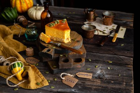 homemade slice of pumpkin cheesecake with caramel sauce and seeds on top on wooden boards on rustic wooden table with assorted small pumpkins Foto de archivo - 133277038