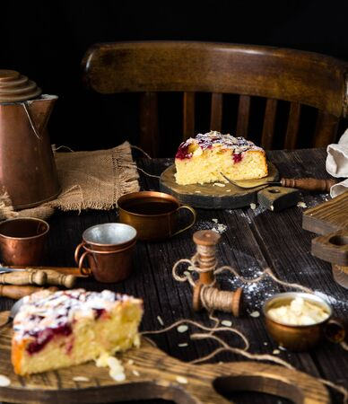 homemade two slices of cake with cherries, almond flakes, powdered sugar on top on wooden boards on rustic table with sackcloth, copper cups and teapot, forks 写真素材