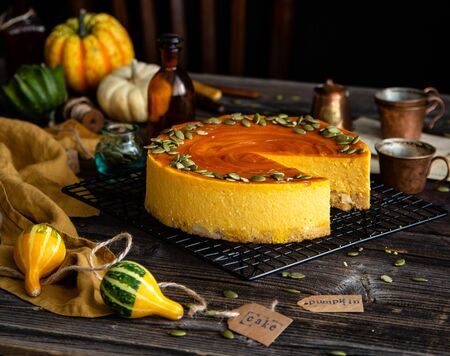 homemade pumpkin cheesecake with caramel sauce and seeds on top on metal wicker stand on rustic wooden table with assorted small pumpkins