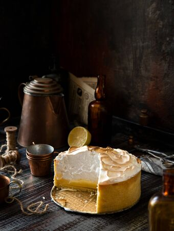 Homemade tasty baked sliced lemon tart with shortbread crust and whipped meringue on top stands on rustic wooden table.