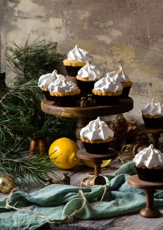 homemade lemon cupcakes with whipped meringue on wooden cake stands on grey table with fir tree branches. christmas sweets Foto de archivo - 133845739