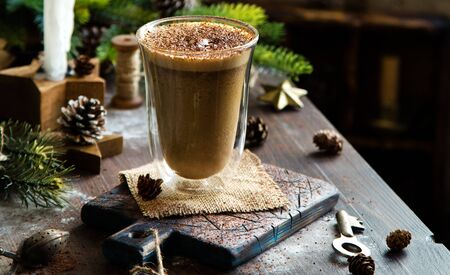 tall glass jar with homemade hot foamy latte on rustic table with fir tree christmas branches Foto de archivo - 133845738