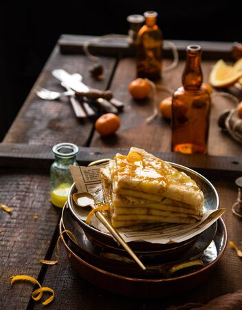 homemade stack of traditional french thin crepes suzette with orange sauce in copper plates on rustic wooden table with old bottles, tangerines, brown napkin Foto de archivo - 133845743