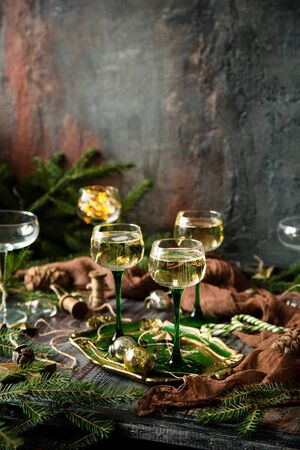 vintage wine glasses with champagne on old wooden green tray stands on rustic table christmas toys, fir tree branches. new year still life Foto de archivo - 133845741