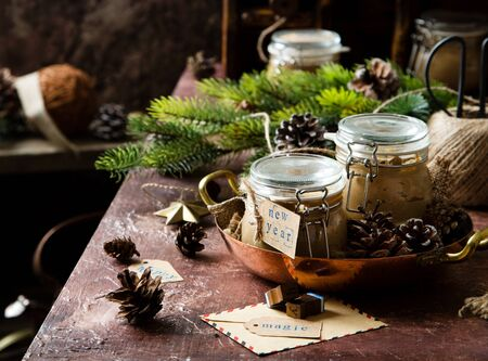 homemade liver pate in glass jars on rustic table with fir tree branches, toys. edible christmas present Foto de archivo - 133845744