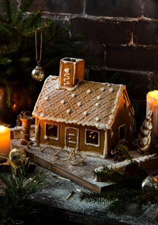 homemade gingerbread house decorated with icing stands on rustic table with candles, fir tree branches Foto de archivo - 133845746