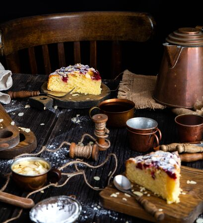 homemade two slices of cake with cherries, almond flakes, powdered sugar on top on wooden boards on rustic table with sackcloth, copper cups and teapot, forks Foto de archivo - 133845752