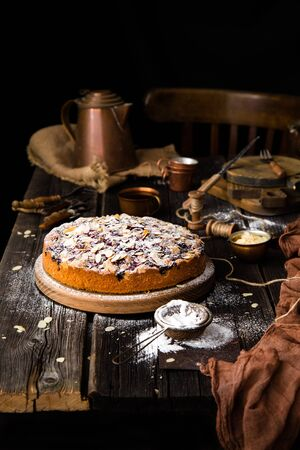 homemade tasty biscuit round cake with cherries, almond flakes, powdered sugar on top on wooden stand on rustic table with sackcloth, copper cups and teapot, forks Foto de archivo - 133845795
