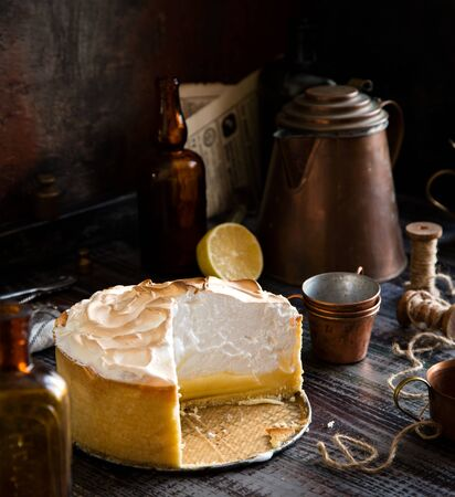 homemade tasty baked sliced lemon tart with shortbread crust and whipped meringue on top stands on rustic wooden table Foto de archivo - 133845754