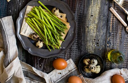 overhead shot of metal vintage plate with fresh green asparagus on rustic wooden table with eggs, salt, grey napkin Foto de archivo - 133845804