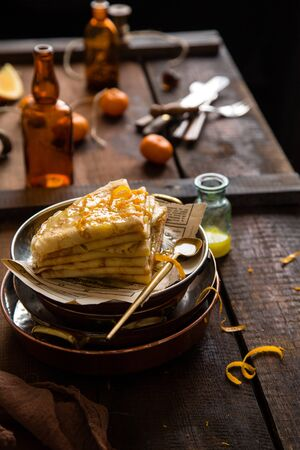 homemade stack of traditional french thin crepes suzette with orange sauce in copper plates on rustic wooden table with old bottles, tangerines, brown napkin Foto de archivo - 133845819