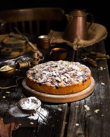 homemade tasty biscuit round cake with cherries, almond flakes, powdered sugar on top on wooden stand on rustic table with sackcloth, copper cups and teapot, forks Foto de archivo - 133845822