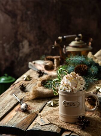 ceramic mug with hot cocoa, chocolate or coffee with whipped cream and christmas candy canes on rustic wooden table with fir tree branches Foto de archivo - 133845823