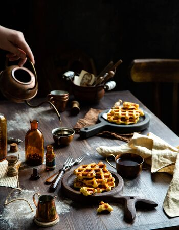 homemade baked waffles with maple syrup or honey on wooden boards stands on rustic table. woman pours coffee  with copper teapot in cup Foto de archivo - 133845828