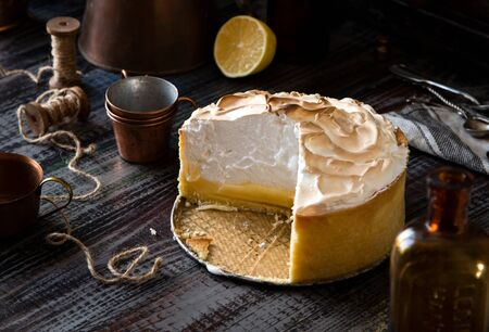 homemade tasty baked sliced lemon tart with shortbread crust and whipped meringue on top stands on rustic wooden table Foto de archivo - 133845830