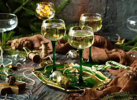vintage wine glasses with champagne on old wooden green tray stands on rustic table christmas toys, fir tree branches. new year still life Foto de archivo - 133845914