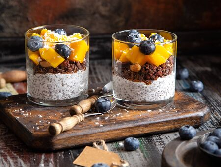 two glasses with healthy layered dessert white chia seeds pudding, chocolate granola, mango, blueberries, coconut flakes Foto de archivo - 133845916