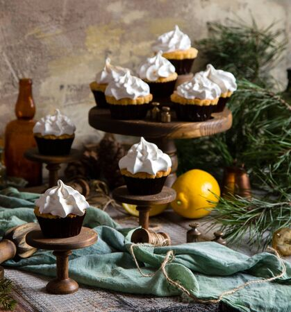 homemade lemon cupcakes with whipped meringue on wooden cake stands on grey table with fir tree branches. christmas sweets Foto de archivo - 133845923