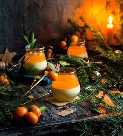 homemade christmas layered dessert creamy panna cotta, jelly or souffle in glasses with small tangerines, fir tree branches on rustic table Foto de archivo - 133845927