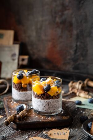 two glasses with healthy layered dessert white chia seeds pudding, chocolate granola, mango, blueberries, coconut flakes Foto de archivo - 133845972