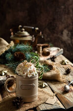 ceramic mug with hot cocoa, chocolate or coffee with whipped cream and christmas candy canes on rustic wooden table with fir tree branches Foto de archivo - 133845975