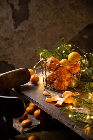 sweet ripe tangerines in golden metal basket on wooden table with fir tree branches and bright garland Foto de archivo - 133845953