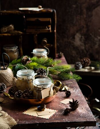 homemade liver pate in glass jars on rustic table with fir tree branches, toys. edible christmas present Foto de archivo - 133845995