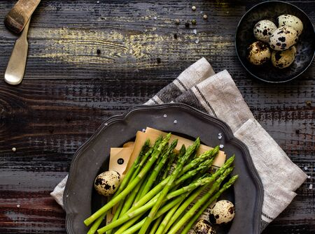 overhead shot of metal vintage plate with fresh green asparagus on rustic wooden table with eggs, salt, grey napkin Foto de archivo - 133846001