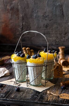 three glasses with healthy layered dessert white chia seeds pudding, mango, blueberries, coconut flakes on rustic wooden table with old bottle of milk, seeds Foto de archivo - 133846005