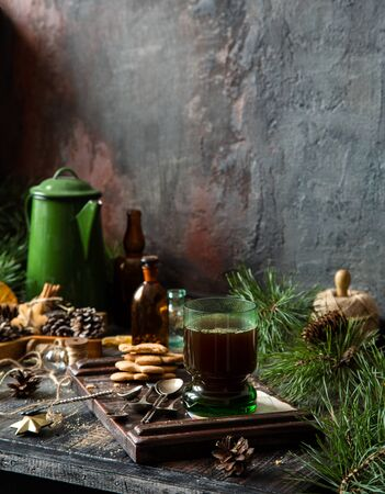 christmas coffee in green glass on rustic wooden table with gingerbread cookies, fir tree branches, green vintage teapot. christmas still life Foto de archivo - 133846011