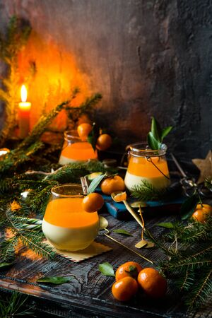 homemade christmas layered dessert creamy panna cotta, jelly or souffle in glasses with small tangerines, fir tree branches on rustic table Foto de archivo - 133846015