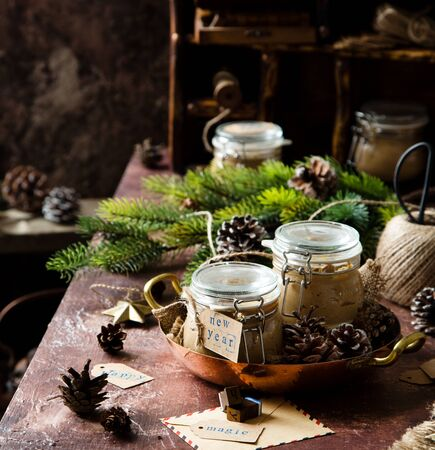 homemade liver pate in glass jars on rustic table with fir tree branches, toys. edible christmas present Foto de archivo - 133846016
