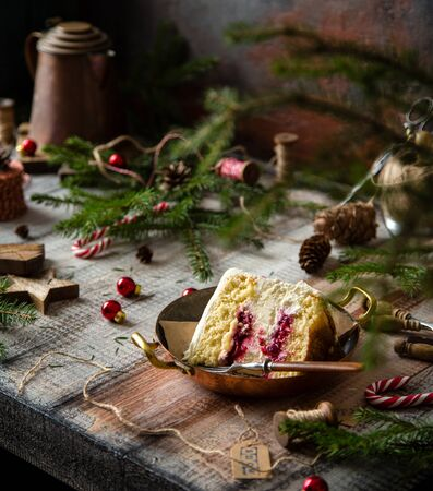 homemade tasty slice of biscuit sponge cake with white cream and cherry sauce inside on copper vintage plate on grey wooden table with fir tree branches, red christmas balls, candy canes Foto de archivo - 133846045